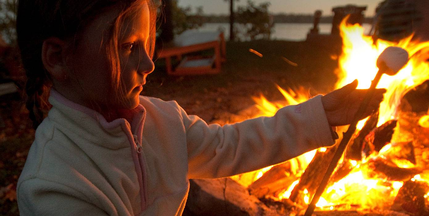 Photo of child by a campfire