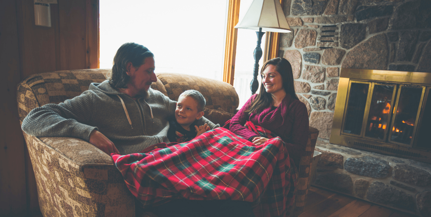 Family on couch by hearth with fire going