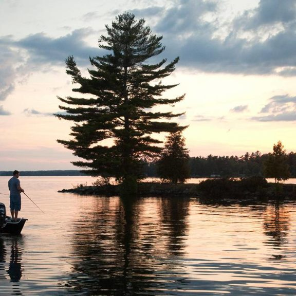 Silhouette of people fishing from a boat in Kawarthas Northumberland