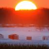 A brilliant orange sun on the horizon illuminates a row of ice fishing huts