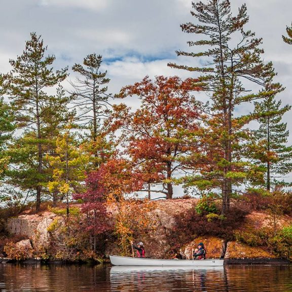 Two canoes glide past a small rocky island, with the treeline showing fall colours
