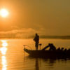 Silhouette of fishermen in a boat with sun reflecting brilliantly in the lake