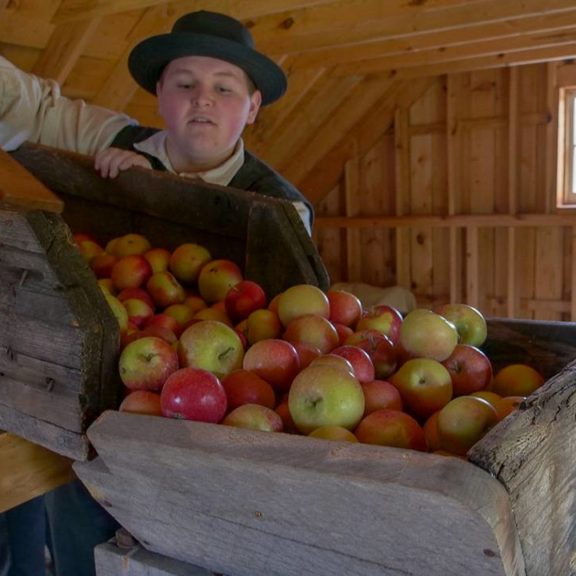 A boy in period dress guides apples into an old-fashioned cider press