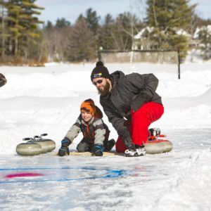 Family curling on frozen lake in the Kawarthas