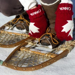 Snow shoer ties old fashion snow shoes.