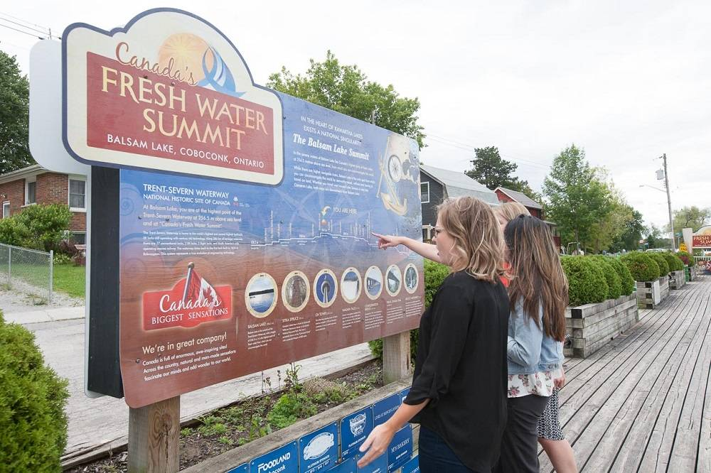 Two people study the Fresh Water Summit sign in Coboconk