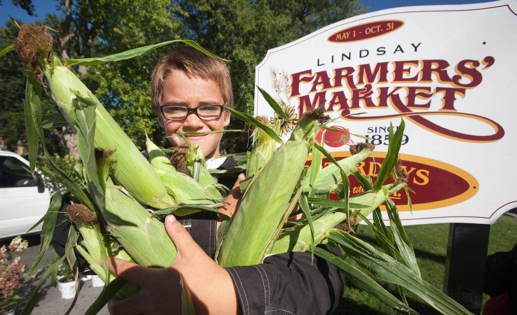 A boy stands with a bushel of corn next to the Lindsay Farmers' Market sign