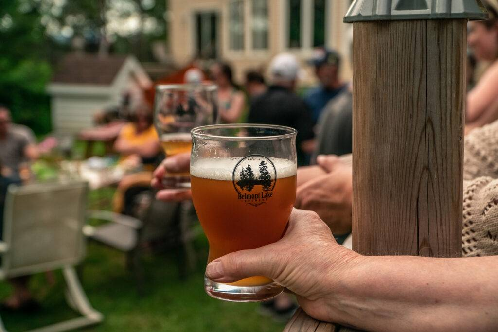 A hand holds a glass of Belmont Lake Brewery Beer