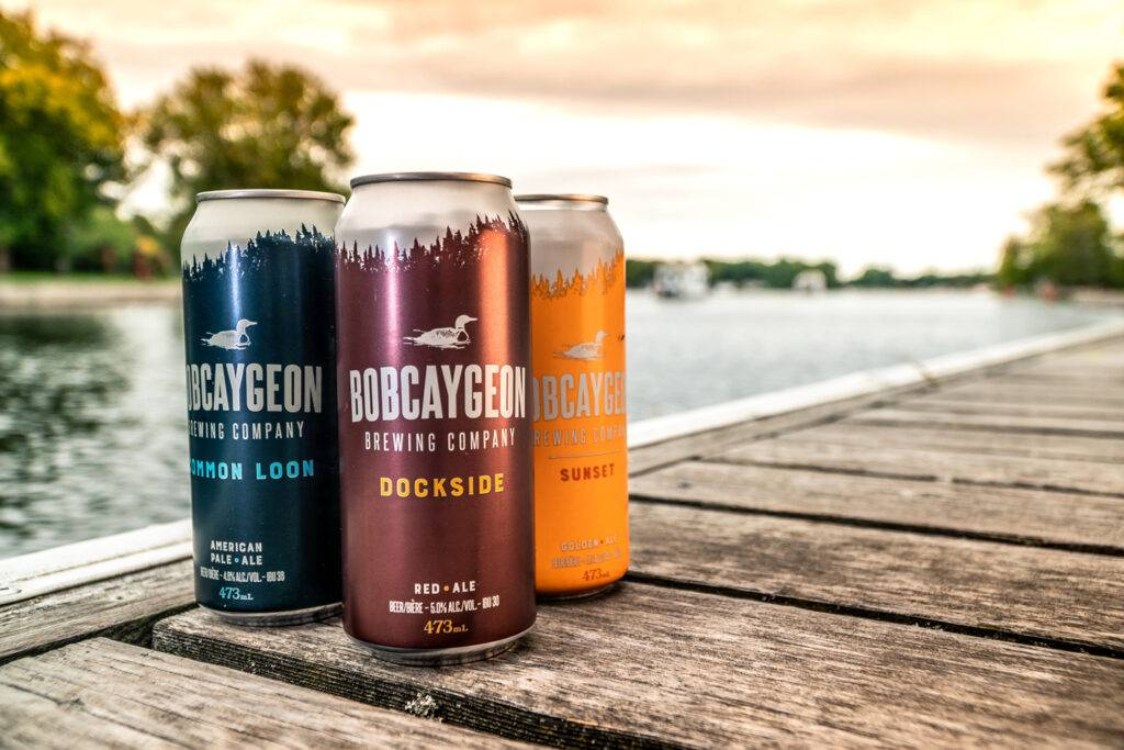 Three cans of Bobcaygeon beer on a dock