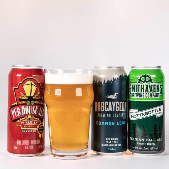 A selection of beer cans and a poured pint from Kawarthas Northumberland craft breweries