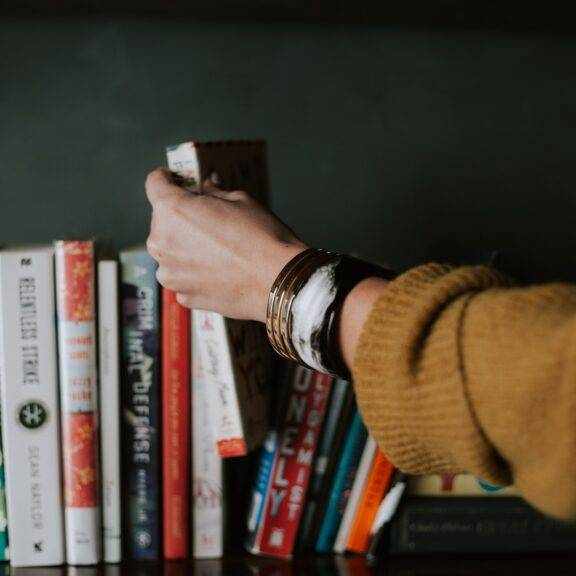 A woman's hand selects a book from a shelf