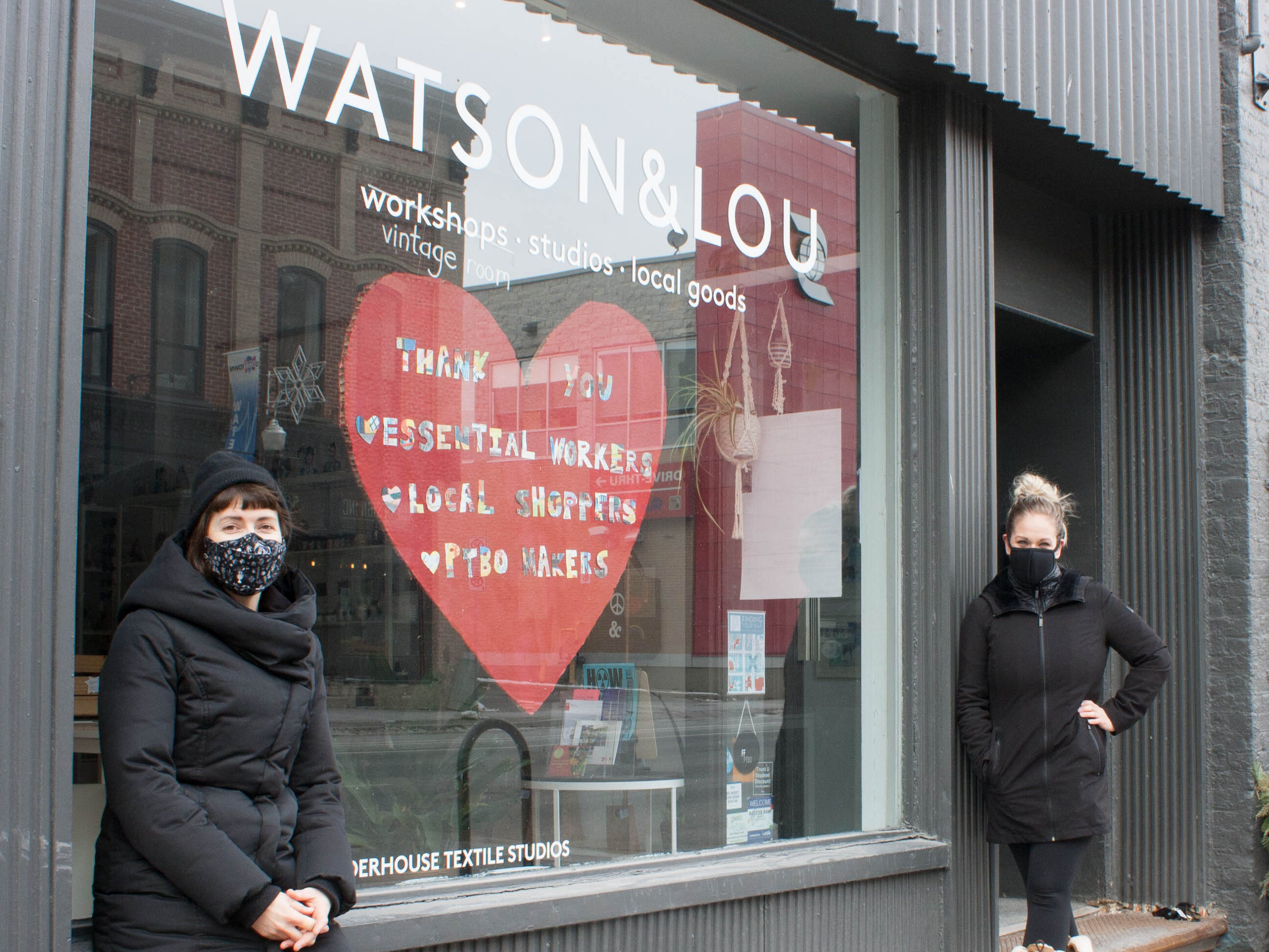 The owners of Watson & Lou stand outside the front window