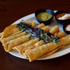 A plate of tacos dorados with sprouts laid over top