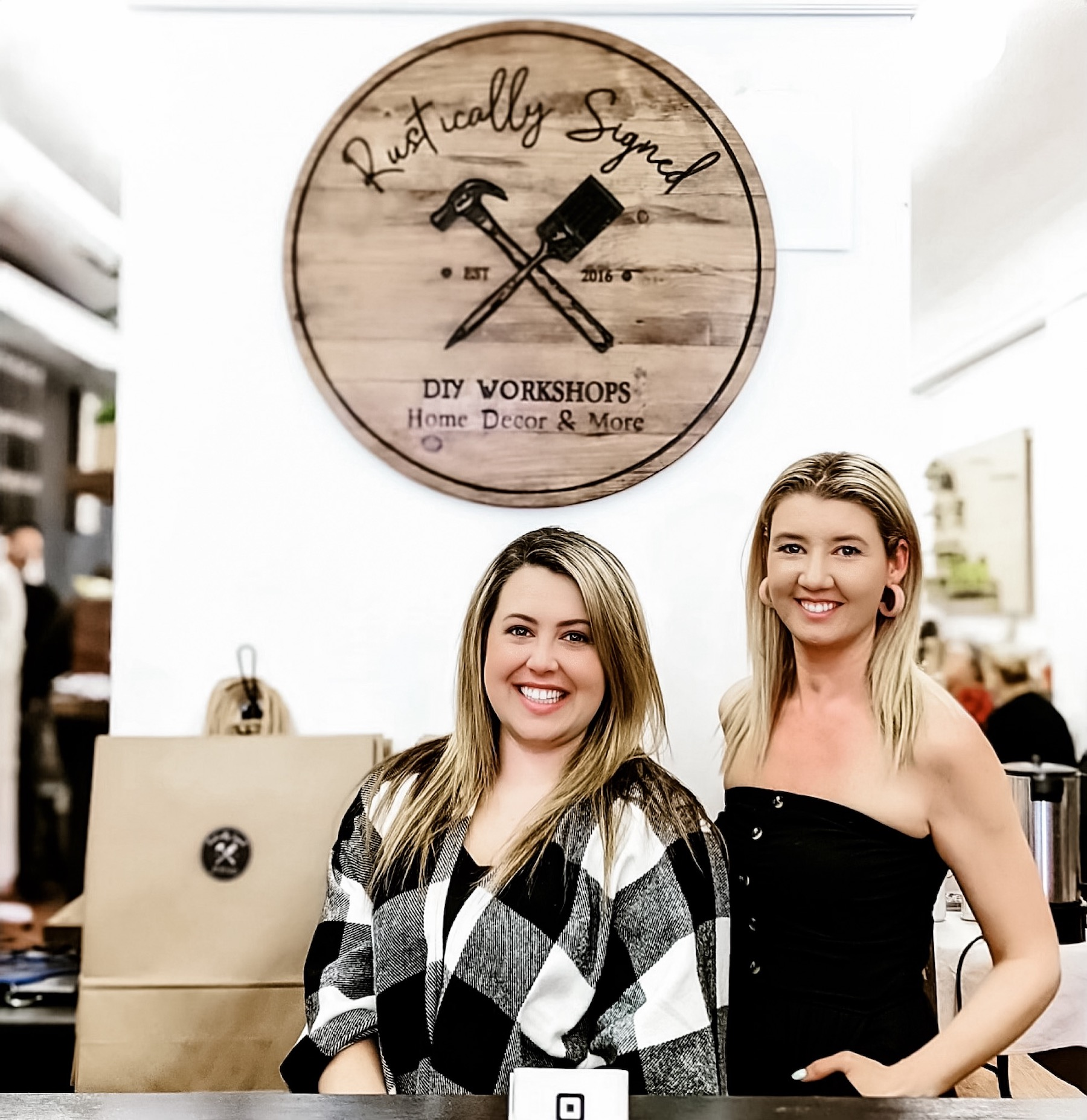Steph Buckley and Holly Suddick stand at the counter of Rustically Signed