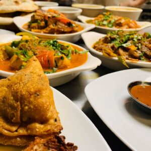 A samosa in the foreground with multiple Indian dishes arrayed in the background