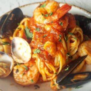 A pasta dish with shrimp, tomato and shellfish