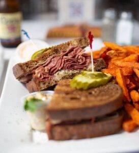 Closeup of a reuben sandwich served with sweet potato fries