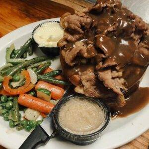 A plate of food with roast beef, mixed vegetables, butter, horseradish, and a steak knife