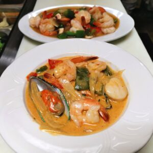 Two dishes of Thai food sit close to the camera, both with thick sauces and shrimp