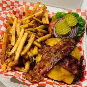 A serving of fries and a burger with bacon sits on a gingham-print paper