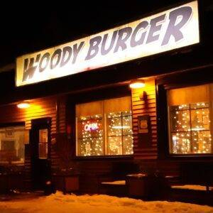 Exterior of Woody's Burger at nighttime, with the sign and windows glowing