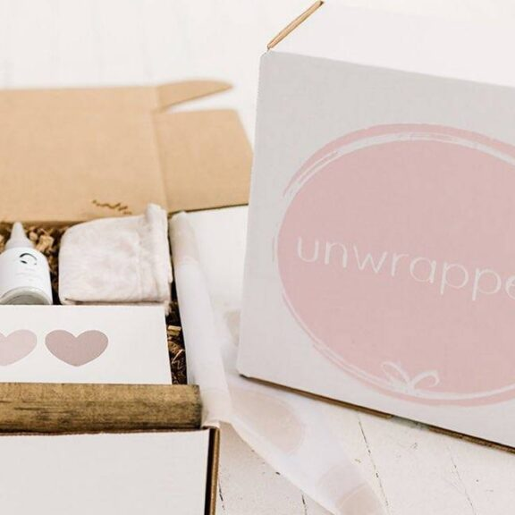 A pink and white box branded Unwrapped, with the lid set to the side and the contents showing, which include a card with hearts, a cloth bag, and a small bottle