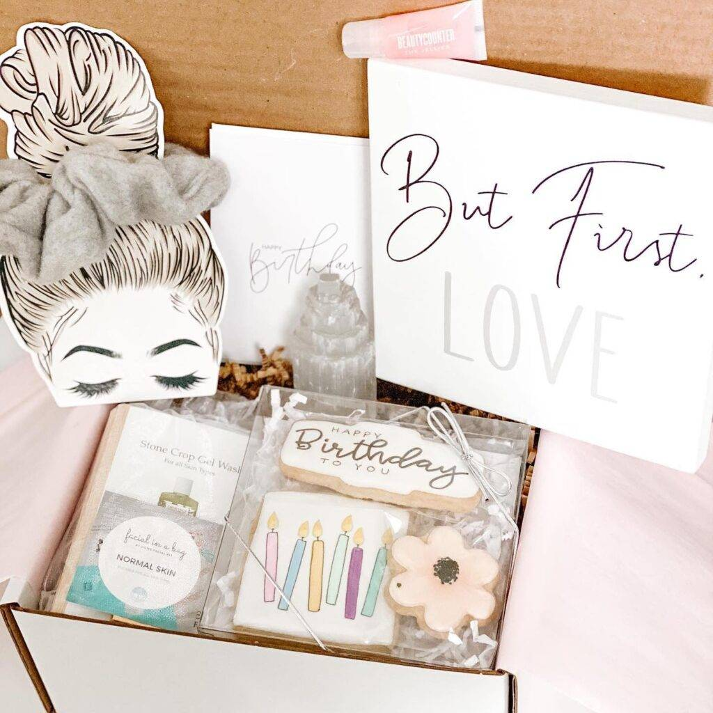 """An open Unwrapped box with assorted contents visible, including """"Happy Birthday"""" shortbread cookies, a scrunchie on a decorative card, a sign that reads """"But First, Love,"""" and a package of skin care product"""