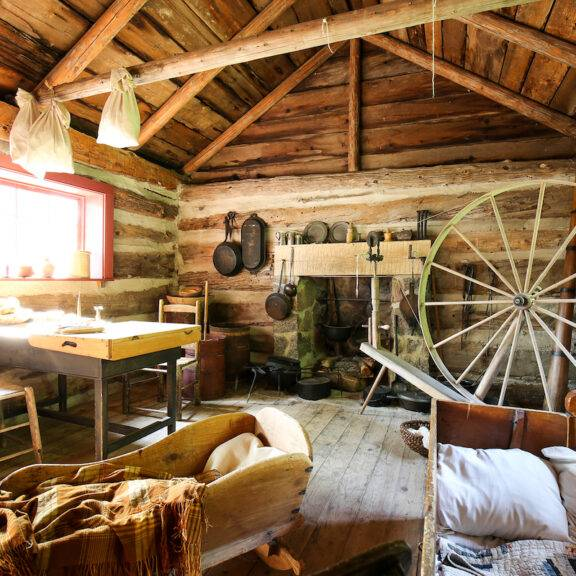 Interior of Fife Cabin at Lang Pioneer Village, showing 1825 period artifacts including spinning wheel, fireplace, and baby crib