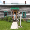 An older woman in an apron climbs the steps of a log cabin at Kawartha Settlers' Village